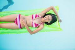 Lycklig kvinna i bikinin som ligger på luftsäng i simbassäng Royaltyfria Bilder