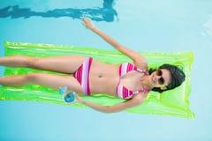 Lycklig kvinna i bikinin som ligger på luftsäng i simbassäng Royaltyfri Foto