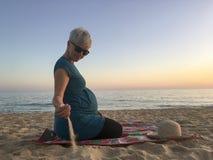 Lycklig kvinna i den nionde månaden av havandeskap som tycker om dur för sandig strand Royaltyfria Bilder