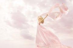 Lycklig kvinna i den rosa långa klänningen, torkduk för halsduk för flickaflyg siden- Royaltyfri Fotografi