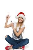 Lycklig kvinna i den Santa hatten som pekar upp Arkivfoto