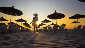 Lycklig kvinna i den vita klänningen och hatten på solnedgången på den tomma stranden Arkivbild