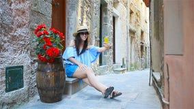 Lycklig kvinna i europeisk semester i Cinque Terre Ung caucasian turist som går på den gamla gatan lager videofilmer
