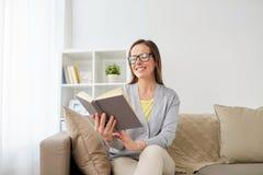 Lycklig kvinna i exponeringsglasläsebok hemma Arkivfoton