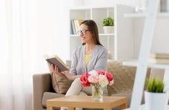 Lycklig kvinna i exponeringsglasläsebok hemma Royaltyfria Bilder