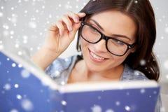 Lycklig kvinna i exponeringsglasläsebok hemma Arkivbild