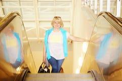 Lycklig kvinna i flygplatsrulltrappa Royaltyfria Foton