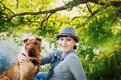 Lycklig kvinna i grov bomullstvilloveraller och hatt med hennes hundShar Pei sammanträde i ängen nära sjön på solnedgången arkivfoto