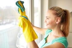 Lycklig kvinna i handskar som gör ren fönstret med trasan Royaltyfria Bilder