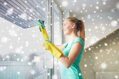 Lycklig kvinna i handskar som gör ren fönstret med trasan Royaltyfri Foto