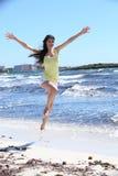 Lycklig kvinna i hoppskott på stranden Royaltyfri Foto