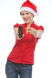 Lycklig kvinna i julhatt som pekar på mobil Arkivbild