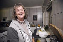 Lycklig kvinna i kök royaltyfri bild