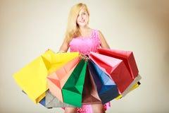 Lycklig kvinna i kort klänning med shoppingpåsar Arkivbilder