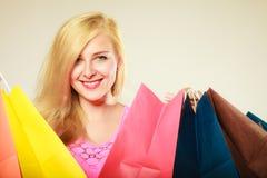 Lycklig kvinna i kort klänning med shoppingpåsar Arkivfoto