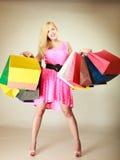 Lycklig kvinna i kort klänning med shoppingpåsar Royaltyfri Foto