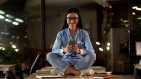 Lycklig kvinna i lotusblommaposition genom att anv?nda mobiltelefonen i regeringsst?llning, avbrottstid p? arbete arkivbilder
