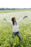 Lycklig kvinna i natur med utsträckta armar i ett blommafält arkivbilder