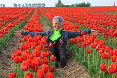 Lycklig kvinna i nederländskt rött tulpanfält arkivfoto