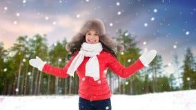 Lycklig kvinna i pälshatt över vinterskog arkivfoton