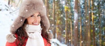 Lycklig kvinna i pälshatt över vinterskog royaltyfri foto