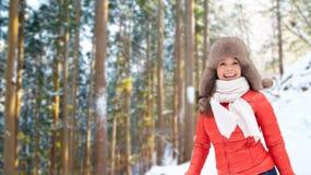 Lycklig kvinna i pälshatt över vinterskog arkivfoto