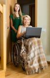 Lycklig kvinna i rullstolen som arbetar på bärbara datorn Fotografering för Bildbyråer