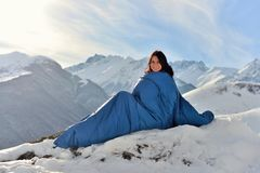 Lycklig kvinna i sovsäck i snöig berg royaltyfri bild