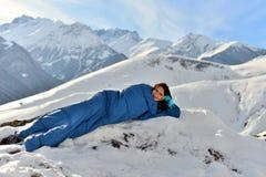 Lycklig kvinna i sovsäck i snöig berg arkivbild