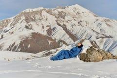 Lycklig kvinna i sovsäck i snöig berg arkivbilder