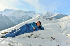Lycklig kvinna i sovsäck i snöig berg royaltyfri fotografi