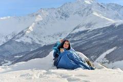 Lycklig kvinna i sovsäck i snöig berg royaltyfria foton