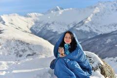 Lycklig kvinna i sovsäck i snöig berg royaltyfri foto