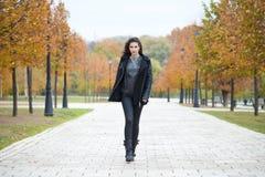 Lycklig kvinna i svart lag som går höstgatan arkivfoton