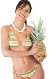Lycklig kvinna i swimwear som rymmer en ananas Royaltyfria Bilder