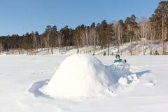 Lycklig kvinna i varm kläder som bygger en igloo på en snöglänta i vintern, Sibirien, Ryssland royaltyfria bilder