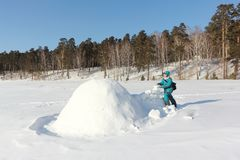 Lycklig kvinna i varm kläder som bygger en igloo på en snöglänta i vintern, Sibirien, Ryssland royaltyfri bild