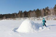 Lycklig kvinna i varm kläder som bygger en igloo på en snöglänta i vintern, Sibirien, Ryssland fotografering för bildbyråer