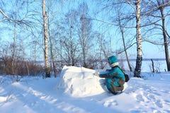 Lycklig kvinna i varm kläder som bygger en igloo på en snöglänta i vintern, Sibirien, Ryssland arkivbild