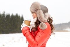 Lycklig kvinna i vinterpälshatt med kaffe utomhus Arkivbild