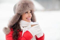 Lycklig kvinna i vinterpälshatt med kaffe utomhus Arkivbilder