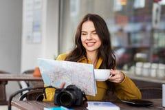 Lycklig kvinna med översikten som dricker kakao på stadskafét arkivfoto