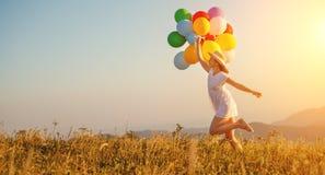 Lycklig kvinna med ballonger på solnedgången i sommar arkivfoto