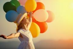 Lycklig kvinna med ballonger på solnedgången i sommar royaltyfria foton