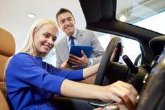 Lycklig kvinna med bilåterförsäljaren i auto show eller salong Royaltyfria Bilder