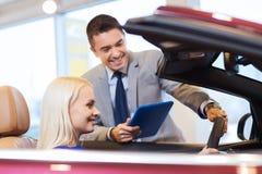 Lycklig kvinna med bilåterförsäljaren i auto show eller salong Arkivfoto