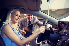 Lycklig kvinna med bilåterförsäljaren i auto show eller salong Royaltyfri Fotografi