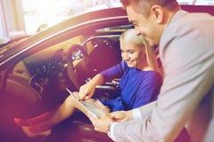 Lycklig kvinna med bilåterförsäljaren i auto show eller salong royaltyfri bild