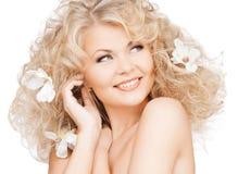 Lycklig kvinna med blommor i hår Arkivbild