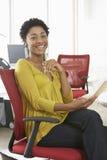 Lycklig kvinna med blyertspenna- och Notepadsammanträde på kontorsstol Arkivbilder